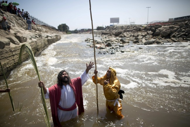 Actors reenact the baptism of Jesus during Holy Week celebrations in the Rimac River in Lima, Peru, Thursday, April 17, 2014.