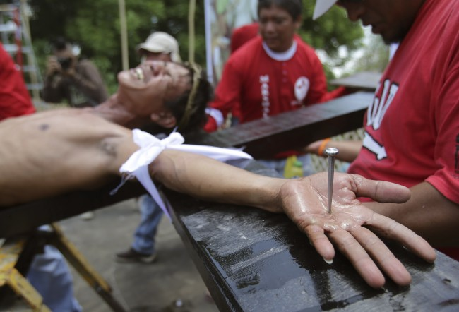 A Filipino devotee grimaces as he is nailed to a cross to re-enact the crucifixion of Jesus Christ in Santa Lucia village, Pampanga province, northern Philippines on Friday, April 18, 2014.
