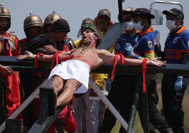 Danish national Lasse Spang Olsen, a 48-year-old filmmaker, grimaces as he is nailed to a cross to re-enact the crucifixion of Jesus Christ in San Juan village, Pampanga province, northern Philippines on Friday, April 18, 201