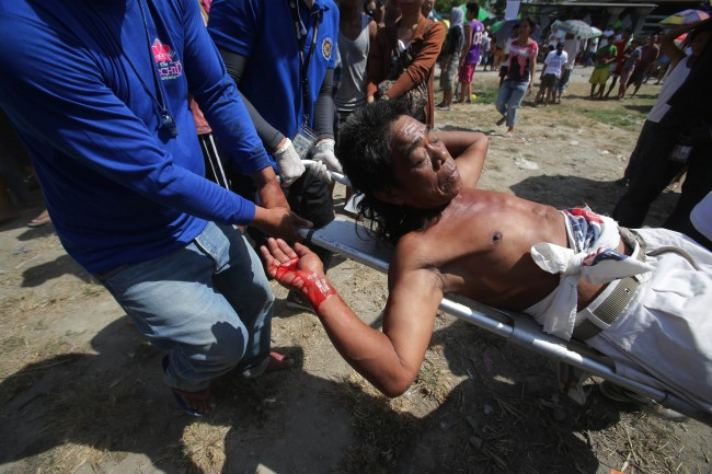 A Filipino devotee who was nailed to the cross is carried by medical personnel after blood comes out of his wounds during a re-enactment of the crucifixion of Jesus Christ in San Pedro Cutud village, Pampanga province, northern Philippines on Friday, April 18, 2014