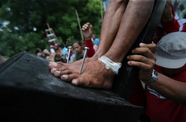 A Filipino devotee with his feet nailed to the cross is lifted as they try to re-enact the crucifixion of Jesus Christ in San Juan village, Pampanga province, northern Philippines on Friday, April 18, 2014.