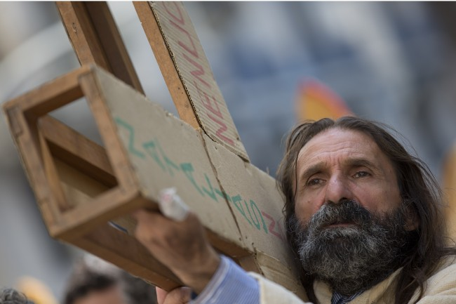 Portraying Jesus Christ, a parishioner reenacts the steps of Jesus' final hours, during a Good Friday procession in downtown Sao Paulo, Brazil, Friday, April 18, 201