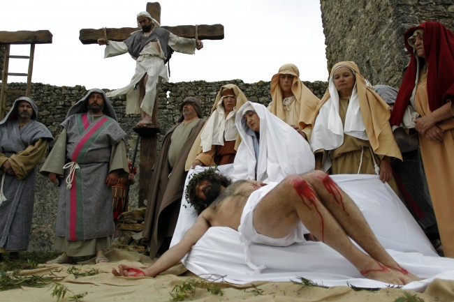 Worshippers perform the Stations of the Cross during the celebrations of the Holy Week in Ourem, Portugal, Friday, April 18, 2014.