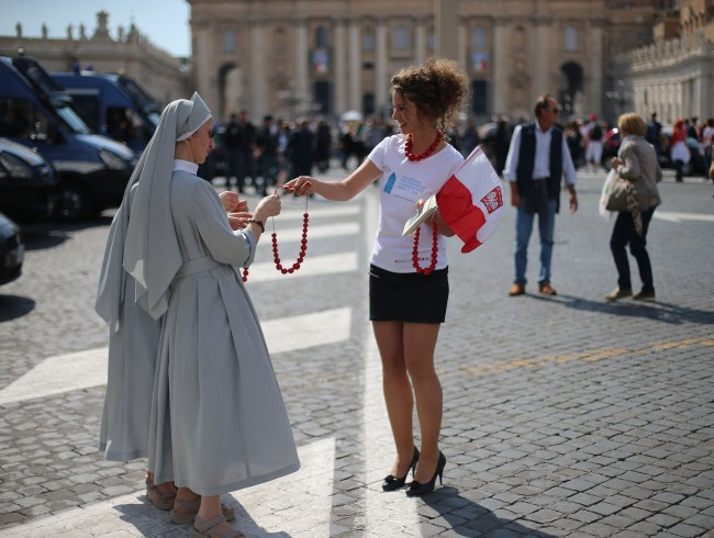 Daria Glownia from the Malopolscka tourist board where Pope John Paul II grew up hands out traditional polish beads to two nuns in St Peter's Square