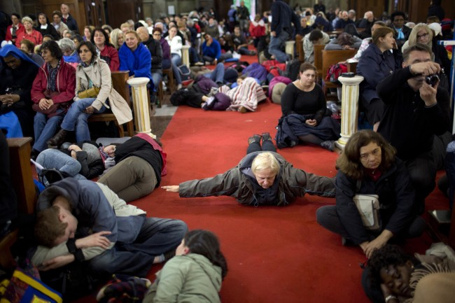 Pilgrims sit and pray inside a church near St. Peter's Square