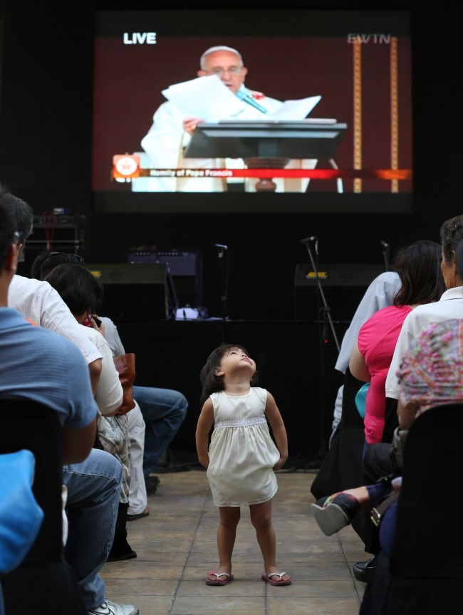 A Filipino girl stands in the crowd as Pope Francis delivers his homily during the live satellite broadcast of the canonization or the elevation to sainthood in the Vatican of Roman Catholic Pope John Paul II and Pope John XXIII on Sunday, April 27, 2014 in suburban Quezon city, north of Manila, Philippines.