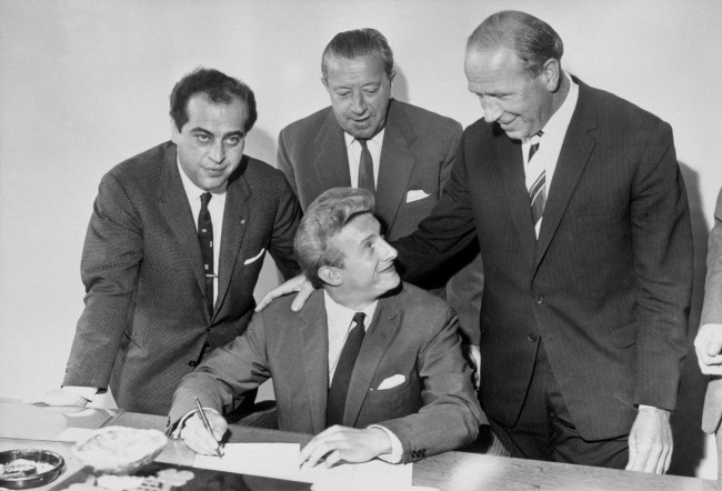 enis Law (c) smiles at Manchester United manager Matt Busby (r) as he puts pen to paper, watched by agent Gigi Peronace (l) and United assistant manager Jimmy Murphy (c, back) Date: 12/07/1962
