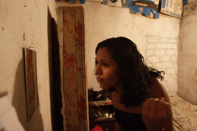 "A prostitute from El Salvador who identifies herself as ""La Flaca,"" or ""Skinny,"" checks her makeup"