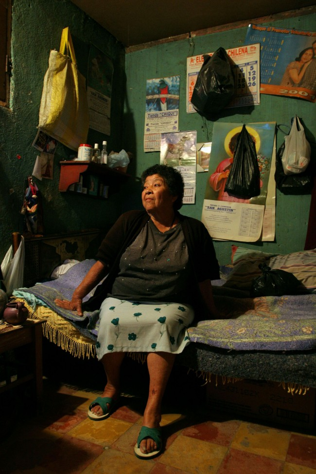 "A sixty-five year old prostitute who identifies herself as ""La Abuelita,"" or ""The Grandmother,"" poses for a portrait in a rented room where she has been living for the last 42 years"
