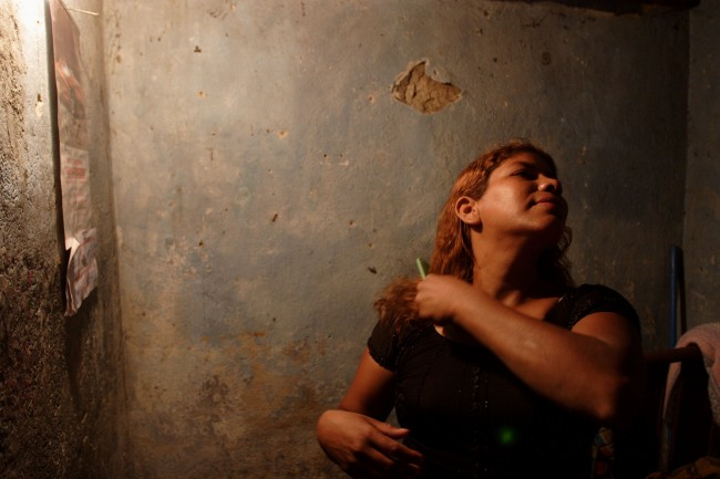 A prostitute from Nicaragua who identifies herself as Mari brushes her hair while waiting for clients
