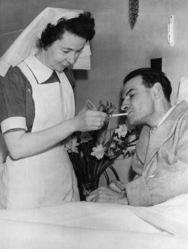 Nurse Nancy Lennox smilingly lights a cigarette for James Blair as he lies in bed today (Sunday) at Bangor Hospital, County Down, Northern Ireland, after being rescued from the disaster to the British Transport Commission's MV Princess Victoria (2,694 tons). The ship foundered in a severe gale five miles off the County Down coast with the loss of over 130 lives. There were about 170 persons aboard.