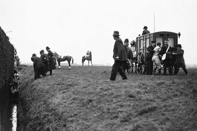 PA 9431325 1 1930 Grand National: Jockey G Goswell Is Helped To An Ambulance As His May King Flounders In The Beechers Brook Ditch