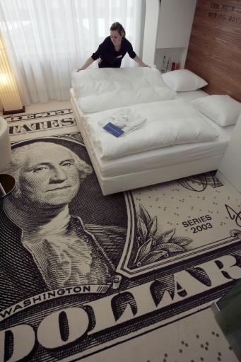 German Katja Bunge, housekeeper of the Wallstreet Park Plaza Hotel, makes a bed in a room with a carpet, looking like a one dollar bill, in Berlin on Monday, March 13, 2006. The rooms and the interior of the new hotel, which is located at the Wallstrasse (Wallstreet) in the German capital, are styled with symbols and themes of the stock exchange at Wall Street, New York.