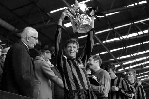 Captain Tony Book holds aloft the FA Cup to the delight of the Manchester City supporters at Wembley, where they beat Leicester City 1-0.