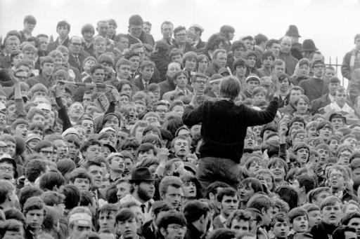 A West Bromwich Albion fan encourages his fellow supporters to sing up in support of their team