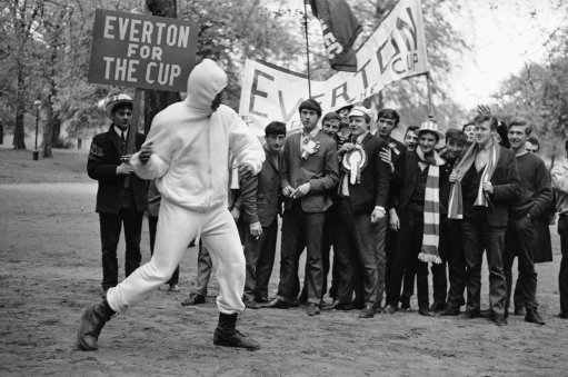 Everton supporters who are in London to see their team play against Sheffield Wednesday in the Football Association Cup final at Wembley on May 14, watch World Heavyweight Boxing Champion Cassius Clay shadow box in Hyde Park, London on May 14, 1966. (AP Photo/Kemp)