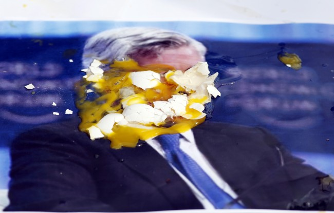 A poster of JPMorgan Chase CEO Jamie Dimon is covered with eggs thrown by protesters, outside the gate of JP Morgan Chase annual stockholders meeting, Tuesday, May 15, 2012, in Tampa, Fla. JPMorgan Chase CEO Jamie Dimon will speak to shareholders five days after disclosing a $2 billion trading loss.