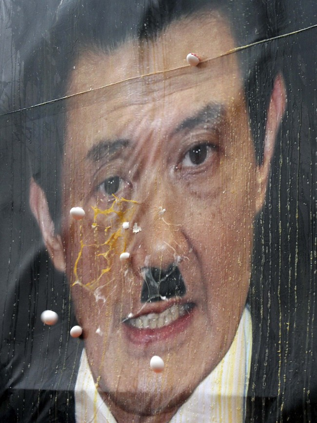 Eggs thrown by anti-government protesters hit a portrait of Taiwan's President Ma Ying-jeou ahead of his inauguration ceremony, in Taipei, Taiwan, Sunday, March 20, 2012. Participants said they were angry about Ma's economic policies, including his decision - announced after his January re-election - to raise utility prices. Ma is to be inaugurated for his second four-year term Sunday.(AP Photo/Chiang Ying-ying)