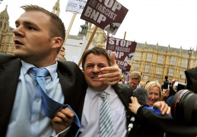 File photo dated 09/06/09 of a bodyguard rushing BNP leader Nick Griffin (centre, grey striped tie) to his car as he abandons a press conference outside the Houses of Parliament in London after protesters barracked him and threw egg