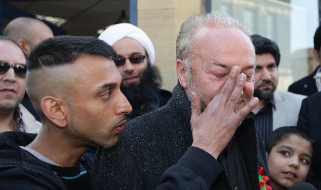 photo dated 30/03/12 of a supporter of George Galloway wiping his face after an egg was thrown towards him before an open top bus tour in Bradford