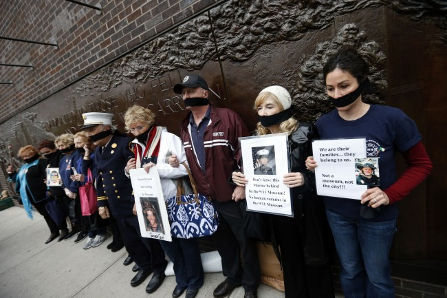 Family members of victims of the Sept. 11, 2001 attacks wear black gags over their mouths in protest of the transfer of unidentified remains of those killed at the World Trade Center from the Office of the Chief Medical Examiner to the World Trade Center site, Saturday, May 10, 2014, in New York. The remains will be transferred to an underground repository in the same building as the National September 11 Memorial Museum.