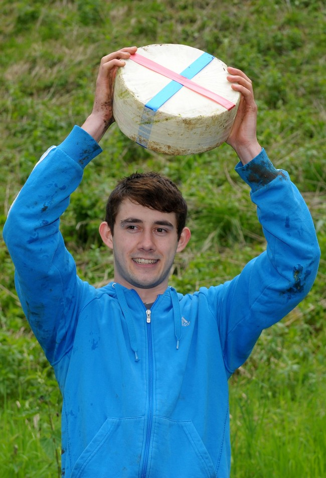Josh Shepherd, 19, from Brockworth, celebrates winning the Men's Downhill race in the Cheese Rolling on Cooper's Hill race near Brockworth, Gloucestershire.