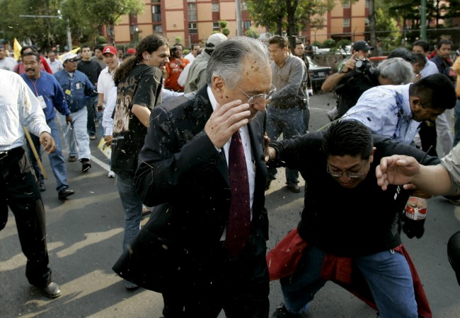 A man gets soiled with mud and raw eggs thrown by protesters as arrives at the Federal Electoral Tribunal, TRIFE as president-elect Felipe Calderon arrives for a symbolic ceremony to mark his designation in Mexico City, on Wednesday Sept. 6, 2006. A day before, the TRIFE had declared that the July 2 elections were valid and that Felipe Calderon had won the presidential race.