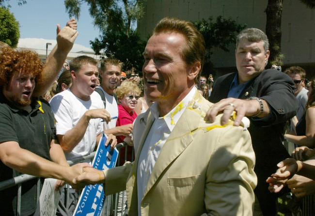 An unidentified aide removes an egg from Arnold Schwarzenegger's coat after it was thrown at him as he arrived at a campaign rally at the campus of California State University, Long Beach, Wednesday, Sept. 3, 2003. Schwarzenegger came to talk about the importance of young people in the political process as he takes his campaign for governor of California.