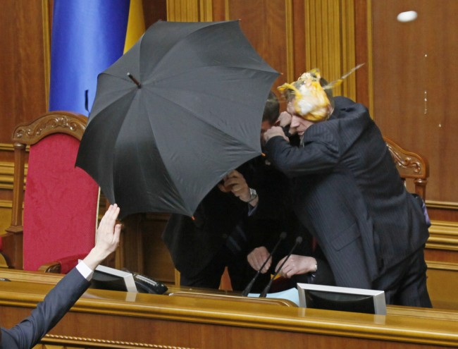 Guards cover parliament speaker Volodymr Lytvyn with an umbrella from eggs thrown by opposition lawmakers during ratification of the Black Sea Fleet deal with Russia, in parliament in Kiev, Ukraine, Tuesday, April 27, 2010. Ukraine's parliament has voted to extend Russia's lease of a Crimean naval port for the Black Sea Fleet in a chaotic session during which eggs and smoke bombs were thrown. The countries' presidents agreed last week to extend the Russian navy's use of the Sevastopol port for another 25 years after the old lease expires in 2017. (AP Photo/Efrem Lukatsky)