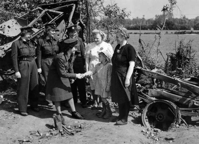 Members of the first WAAF contingent to arrived being greeted by French people in Normandy on August 6, 1944. In the back ground is a burnt-out German motor vehicle. Section Officer J. Bradbury of Hale, Cheshire is shaking hands with the child; looking on from left to right are Cpl. J.J. Disney of Denton, Norfolk, L.A.C.J. Davis, of Dalson, London E.8. and Sgt. M.D. Easson of Edinburgh. (AP Photo)