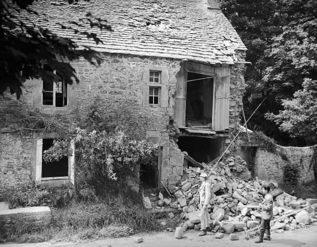 Two French civilians look over the wrecked birthplace of the French painter, Jean-Francois Millet in France on August 28, 1944. The house was situated at Gruchy near Greville, which was one of the most heavily fortified regions on the Normandy coast and the scene of many bitter battles before it was liberated by the Americans. Many Nazi soldiers were taken prisoner near here. (AP Photo/Lawrence Riordan)