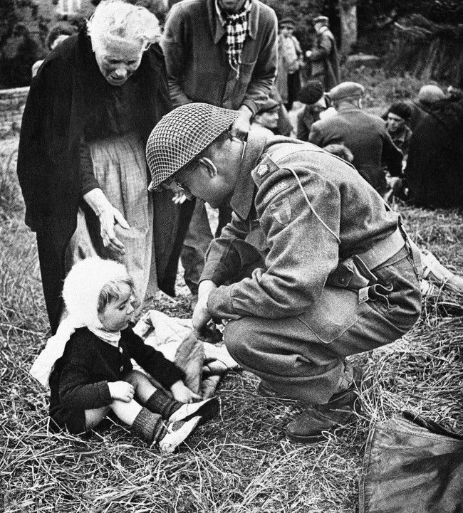A Canadian soldier, serving with the British forces in Normandy, France, strikes up an acquaintance with a little French girl on Sept. 7, 1944, one of a group of refugees that were fed by the liberating armies. The feeding arrangements were organized by the Civil Affairs. (AP Photo)
