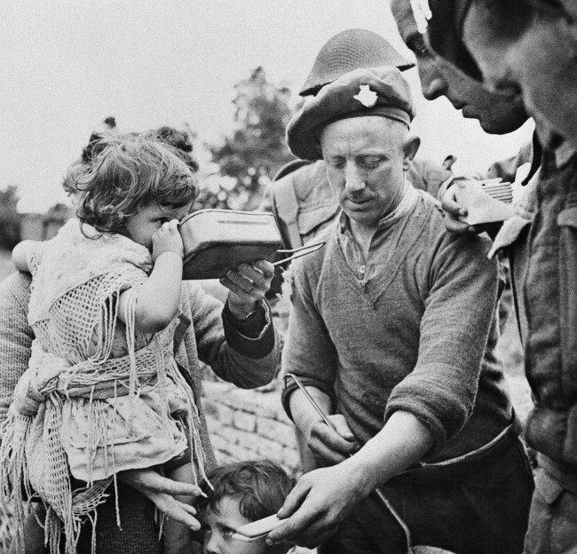 French refugees, including women and children, gather around British soldiers at a Civil Affairs Feeding Center in the Normandy beachhead sector who are supplying hot food on June 16, 1944. Many of the refugees had not eaten for three or more days. (AP Photo)