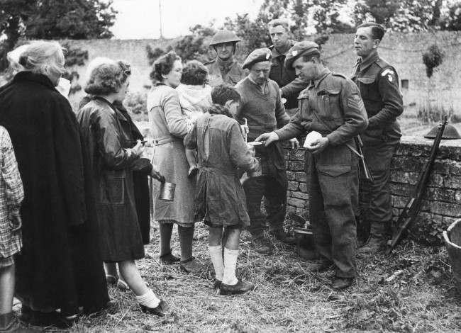 Many of the French refugees had not eaten for three or more days. They are seen receiving food from British troops in France on June 12, 1944. The feeding arrangements were organized by the Civil Affairs Department. (AP Photo)