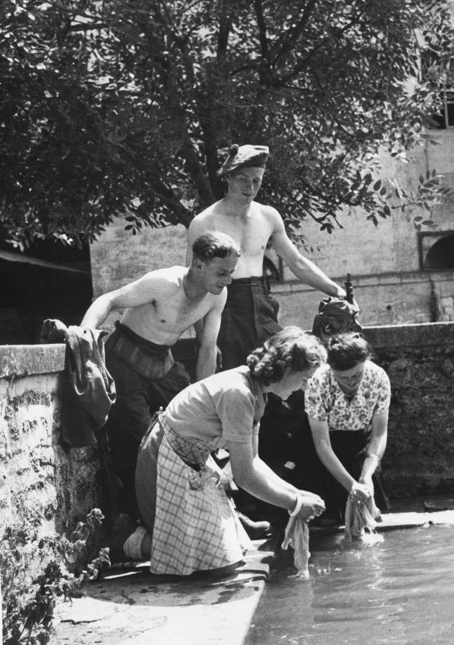 Two British soldiers taking part in the liberation of France from the Germans are rewarded by Frenchwomen, of a Normandy farm, by having their laundry washed for them in France on July 15, 1944. (AP Photo)