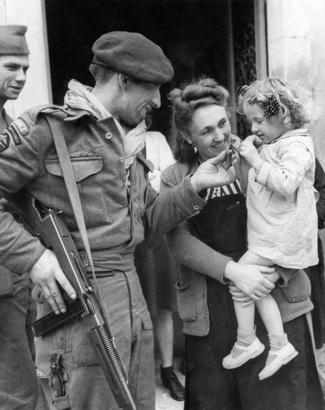 French villagers welcomed members of a French Commando who landed in Normandy in Amfreville, North of Ranville on June 17, 1944. Chester Wilmot, BBC commentator was also there at the time. A French Commando greeting a little girl who had been brought out to see him. (AP Photo)