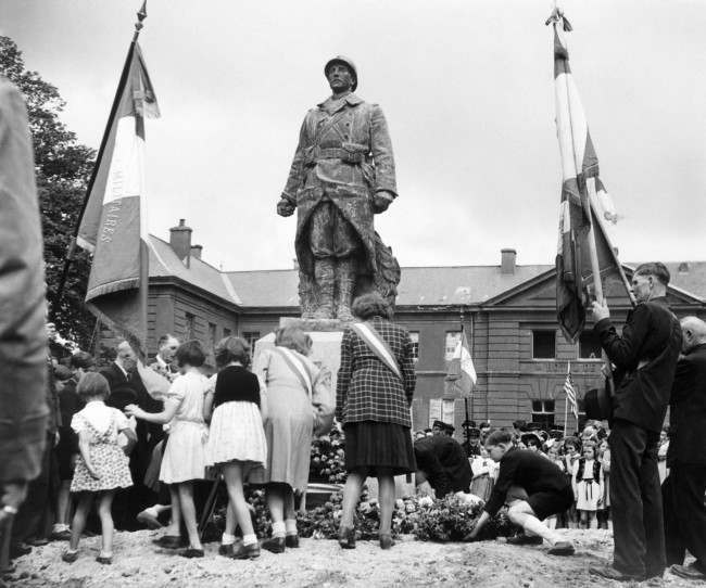 Bastille Day celebrations in the little Normandy town of Isigny on July 19, 1944 took the form of services at the town's War Memorial. French children pass in turn to lay their tributes to war dead at the War Memorial during the services. (AP Photo/Bert Brandt)