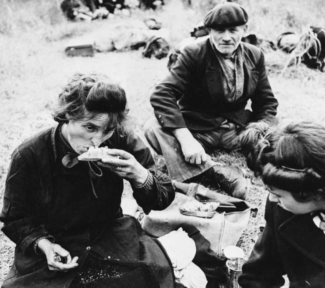 Many of these French refugees had not eaten for three or more days. In a field behind the allied lines they rest and receive food from our troops on June 20, 1944. The feeding arrangements were organized by the civil affairs dept. (AP Photo)