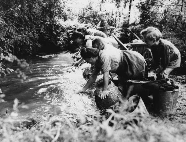 French children watch their mothers wash clothes in a brook in Normandy on August 23, 1944 in an area liberated from the Nazis by American Forces. (AP Photo/Lawrence Riordan)