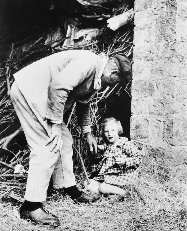 A bright-eyed little French girl is persuaded to leave the spot, behind a pile of branches, where she made her home when the Allies swept into her community in Normandy on June 15, 1944. (AP Photo)