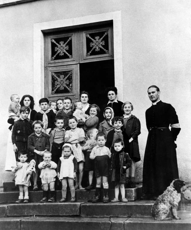 "French war orphans ""somewhere in Normandy"" with Abbe Noe, Parish priest, at the new French colony opened by the Foster Parents plan for war children on Dec. 11, 1944. The children had one blanket for all and were living on a diet of coffee and stale bread when they were found by Lieut. Bishop Marshall, plan representative in France. (AP Photo)"