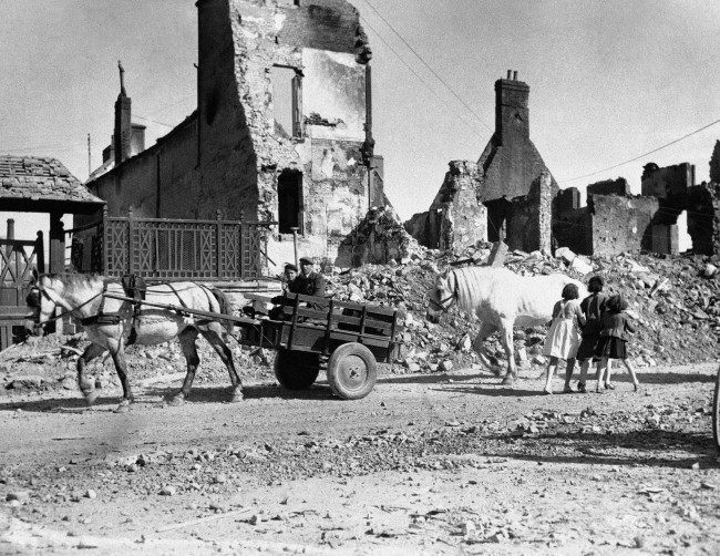 Natives of a French village shattered by the Normandy invasion fighting move down a road past ruined buildings on June 15, 1944. (AP Photo)
