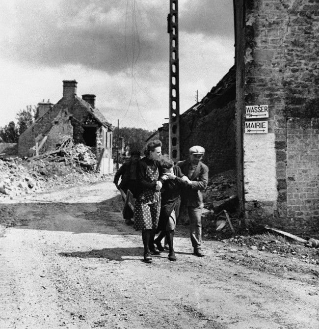 Two friends assist a weeping woman (center) in the Normandy village of Ste. Marcouf on June 19, 1944, after her husband was killed when the Germans shelled the place. The man's body is inside the store at right, upon which the Germans placed two signs: Wasser (German for water) and Mairie (French for town hall). (AP Photo)