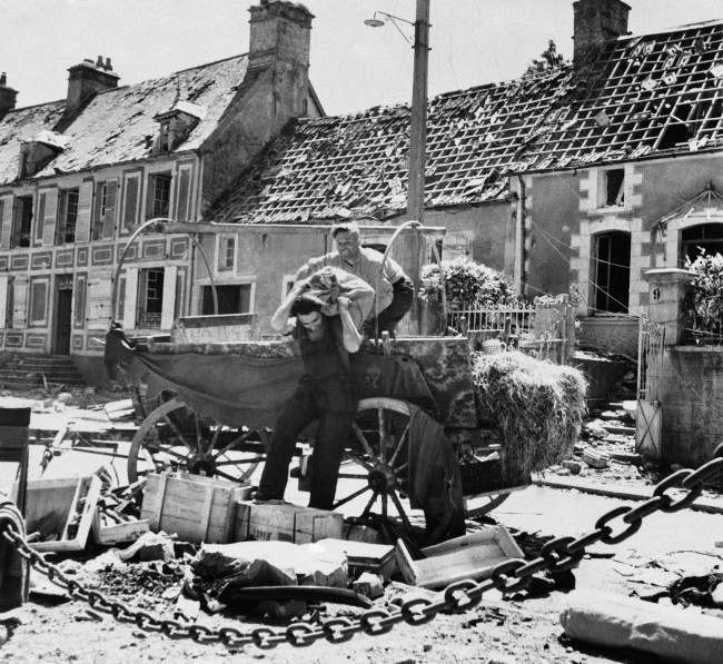 Two French civilian refugees from the battle that raged in St. Sauveur as American troops advanced on Cherbourg on June 23, 1944, unload their cart after returning to their homes. House in background, with most shingles gone. (AP Photo)