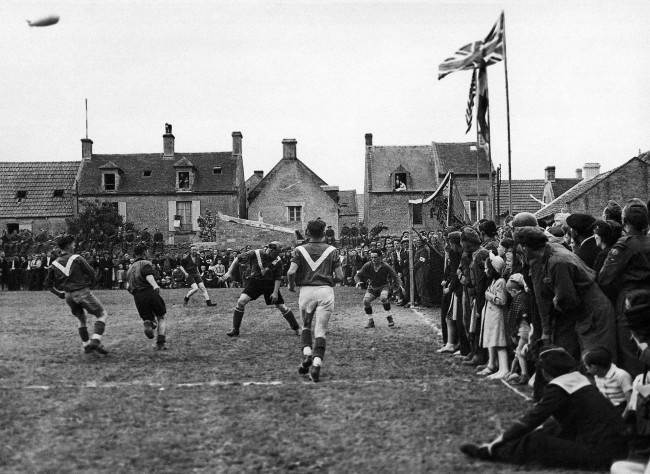 For the first time since 1939, French men and women in the liberated towns and villages of Normandy were able openly to celebrate on July 14th, Bastille Day, without fear of German reprisals. In the little town of Coursoulles near the coast, where this picture was taken in July 1944, British troops played a football match against the local French team and all the towns folk turned out to watch the game. The match in progress with enthusiastic spectators crowding the touch-line. (AP Photo/Photographic News Agencies, LTD.)