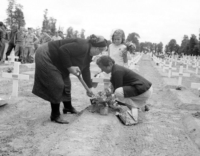 A French family living in the La Cambe area of Normandy, France on July 15, 1944, now liberated by the allies, place flowers on the graves of the U.S. dead as part of the Bastille Day celebrations. (AP Photo/Bede Irvin)