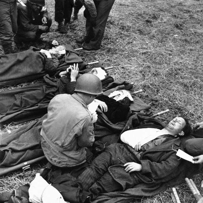 rench civilians, wounded during the Normandy battles on June 19, 1944, lie on stretchers on the ground behind the lines, where they are treated by U.S. Army medical corpsmen. (AP Photo)