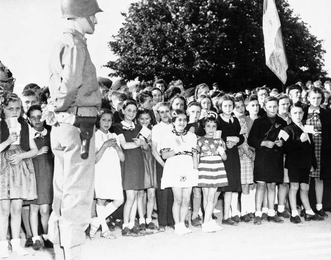 French children of the Normandy town of Grandcamp, France, some carrying American flags and others dressed in patriotic costumes, join American occupation troops in celebrating the American Independence Day on July 4, 1944. Many residents turned out for the ceremonies in the village, which was the first to be liberated by the invading allied forces. (AP Photo)