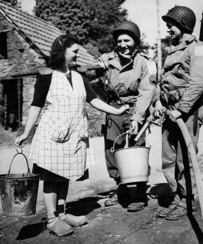 Two American soldiers, Staff Sgt. Bernard Dargols, New York, and Tech., 5/c William L. Stanley, Houston, Texas, right, help a French farm girl fill her water pails from an army water purification unit during a quiet moment somewhere in the Normandy beachhead area of France on June 30, 1944. (AP Photo)