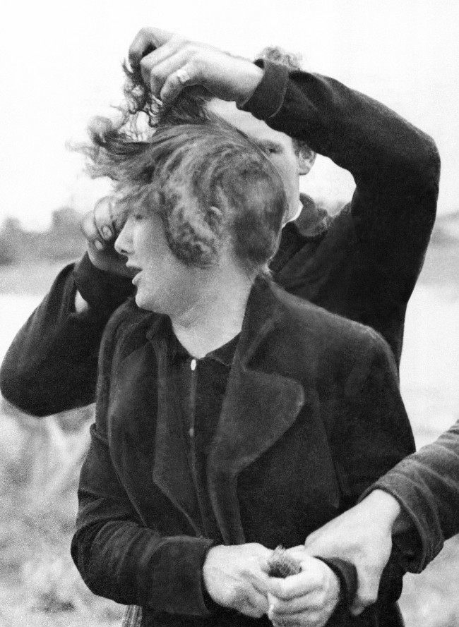 Grande Guillotte, 23 year-old-French girl collaborated with the Germans in Normandy. When her town was liberated by Allied troops, French patriots dragged her from her house and cut off all her hair. A French patriot cuts off Grande Guillotte's hair while another holds her in France on July 7, 1944. (AP Photo)